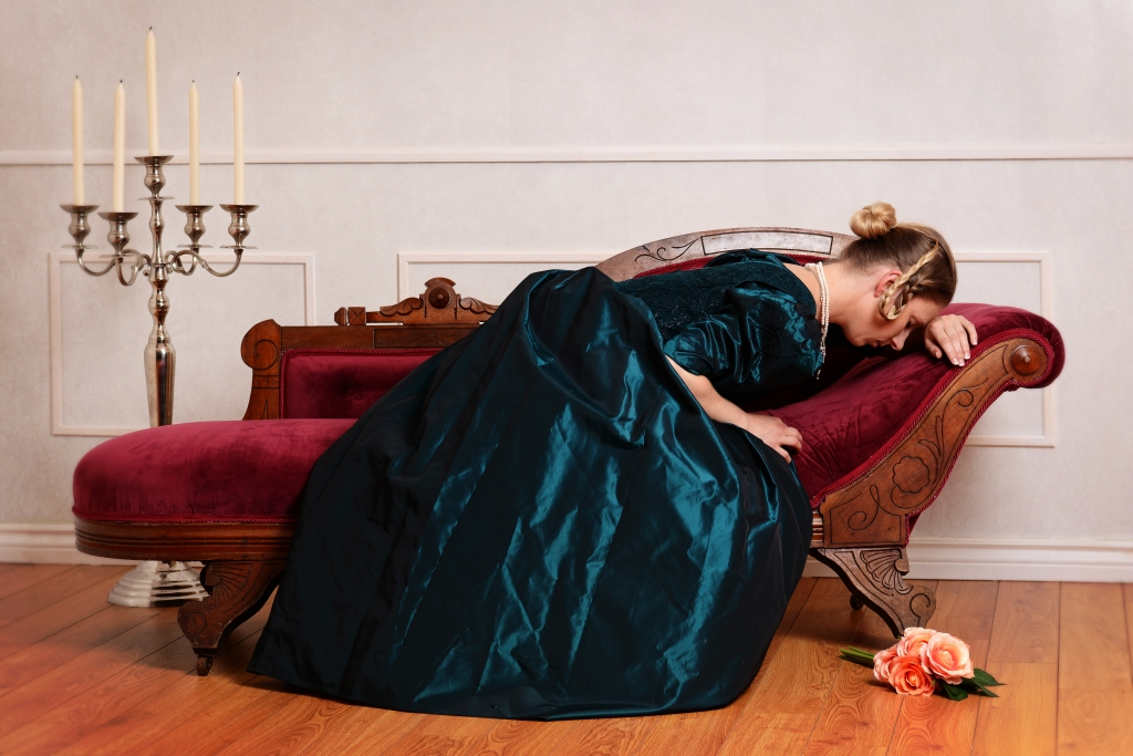 Victorian woman in green velvet dress  lying face down on a fainting couch